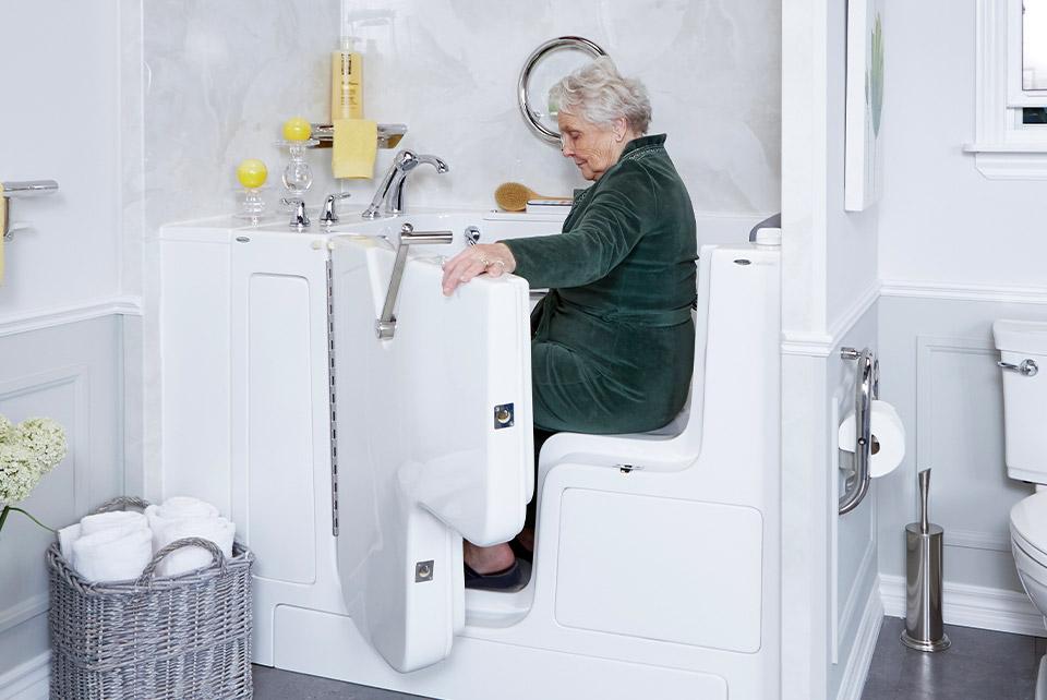 An elderly woman sitting in a walk-in bathtub